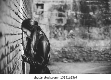 Angry and pensive adult young woman leaning head against a brick wall, reflecting on her sadness and inner personal crisis.
