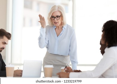 Angry powerful mature businesswoman boss scolding employees frustrated by bad work results in office, dissatisfied female middle aged executive rebuking diverse workers at group corporate meeting