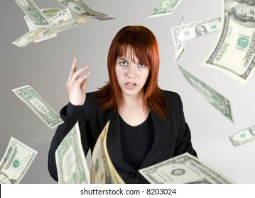 Angry and pretty redhead girl throwing Dollar banknote money towards the camera.
