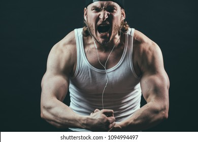angry professional bodybuilder taking part in the competition, close up cropped photo