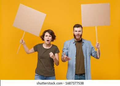 Angry protesting young two people guy girl hold in hands protest signs broadsheet blank placard on stick isolated on yellow background in studio. Protests strikes pickets concept. Youth against city