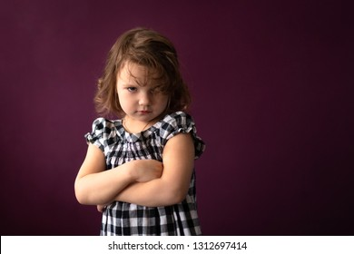 Angry sad girl child in a dress in a cage against a dark background. Concept childhood and emotions, berry color