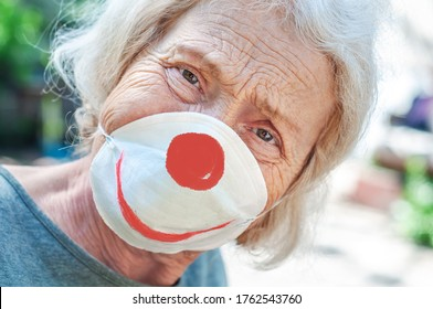 Angry sad grandmother elderly woman in a respiratory mask with a painted funny clown mask. Tired of wearing a mask. Old lady makes fun of wearing a mask, covid-19. Concept of deception coronavirus