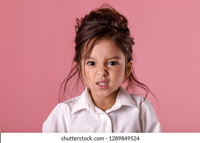 angry screaming little child girl in white shirt with hairstyle looking to camera on pink background. Human emotions and facial expression