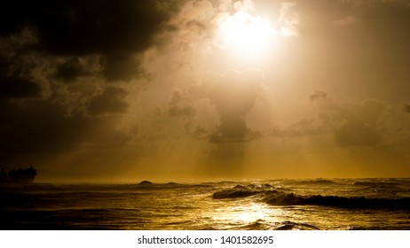 Angry seas at sunset and crashing waves on rocks with sun rays through cloudy skies God Rays Faith Hope danger powerful nature heavy seas blue oceans orange skies blue and aqua waters rocky shores