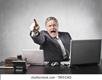 Angry senior businessman sitting at his desk and screaming