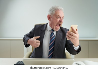 Angry senior white collar worker wearing classical suit sitting at office desk and shouting at smartphone after stressful talk with his boss, office interior on background