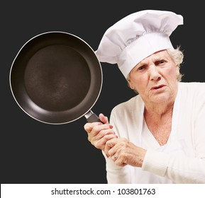 angry senior woman cook trying to hit with a pan over a black background