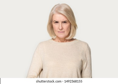 Angry senior woman isolated on grey studio background look angrily at camera with grimacing mad face, dissatisfied mature lady show irritation and discontent, having bad mood negative emotions