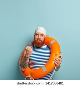 Angry serious red haired man shows fist as threatens to revenge, uses throwing aid during water recreation, wears white swimhat and sailor striped t shirt, poses over blue wall with blank space above