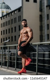 An angry sexy sportsman stands topless near the wall. Fitness, bodybuilding. Signature.