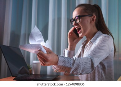Angry, shouting business woman emotionally talking on the phone and crumpling documents during hard project working. Business problem concept nervous work.