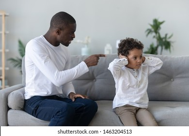 Angry single black father scolding stubborn fussy little african son closing ears not listening ignoring dad punish small mixed race kid boy for bad behavior, parent and child family conflict concept