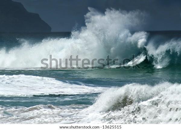 Angry spray and foam sail skyward as wild waves pound the coastline off Kauai, Hawaii.
