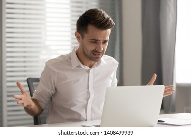Angry stressed business man annoyed by computer problem in office looking at stuck slow laptop feeling mad crazy, furious businessman frustrated by data loss, system virus or application failure