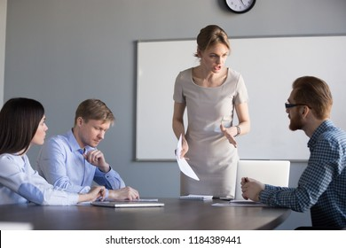 Angry strict executive, female ceo or team leader scolding unprofessional employees frustrated by bad work results in financial report shouting reprimanding stressed worker at group corporate meeting