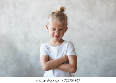 Angry stubborn Caucasian male kid with hair knot crossing arms on his chest and grimacing, expression unwillingness and protest towards doing something he doesn't want. Disobedient boy wrinkling nose.