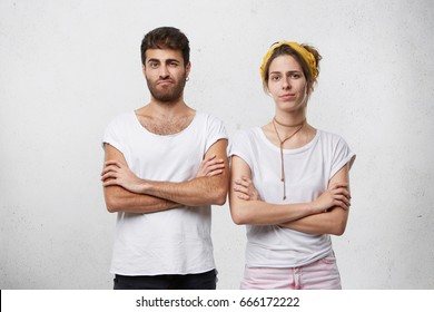 Angry stubborn man and woman standing in closed postures, keeping arms folded, facing disagreement in relationships while having conflict or quarrel, or expressing disapproval, skepticism and distrust