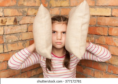 Angry, stubborn, sad, upset little girl is sitting near the brick wall and closing her ears with pillows