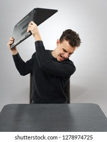 Angry student smashing his laptop on the table