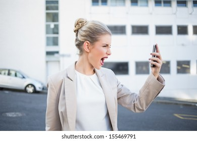 Angry stylish businesswoman shouting at her phone outdoors on urban background