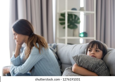 Angry sulky child girl and annoyed mother sitting back to back on sofa not talking after fight, stubborn kid daughter pouting ignoring mom upset by quarrel, family conflict disagreement concept