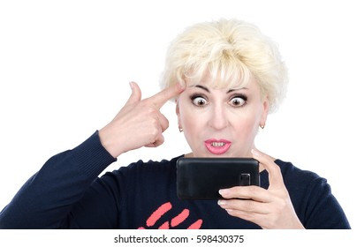 Angry surprised middle aged blonde woman has video call chat with mobile phone. Furious blonde with big eyes puts finger to her temple. She shows gesture gun. Mid-shot on white background