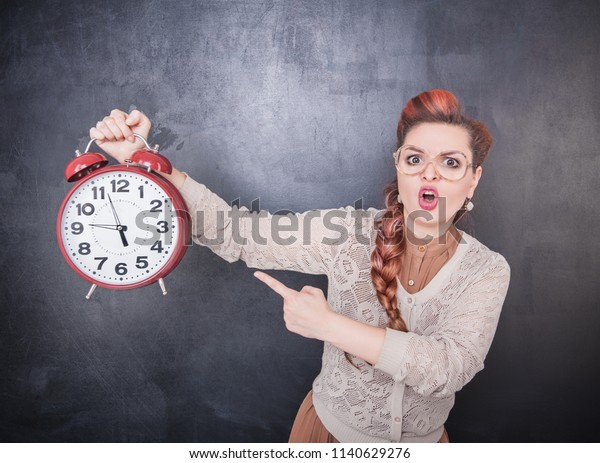 Angry teacher with clock on the chalkboard blackboard background
