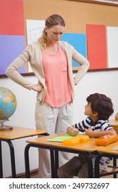 Angry teacher looking pupil with hands on hips at the elementary school