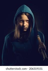 Angry teen girl in hood with baseball-bat