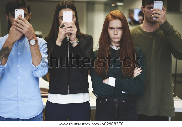 Angry teen hipster girl disappointed about being alone as her friends active in social networks creating life and personality in social networks using smartphones and free wireless internet connection