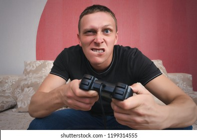 Angry tense gamer man with gamepad in the hands is playing in video game. A tense game.