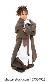 Angry three year old mixed race girl standing in baggy suit with arms crossed over white background.