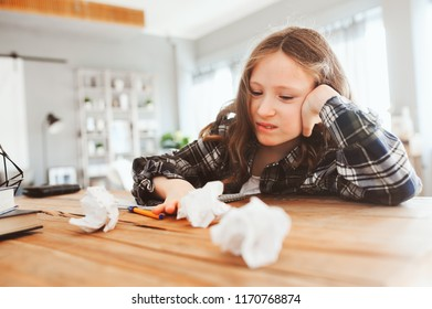 angry and tired child girl having problems with home work, throwing papers with mistakes. School and education concept. Difficult lessons.