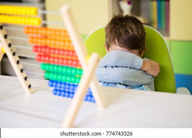Angry toddler boy making a tantrum refing to play with abacus. Concentration deficit. Early child development.