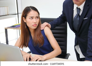 Angry unhappy Asian secretary woman looking hand's boss touching her shoulder in workplace. Sexaul harassment in office