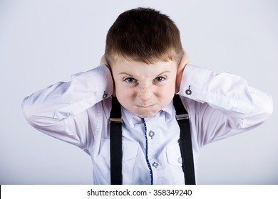 Angry, unhappy, irritated little boy covering ears, looking to camera over white background.