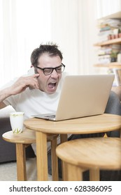 Angry unhappy man sitting in front of laptop