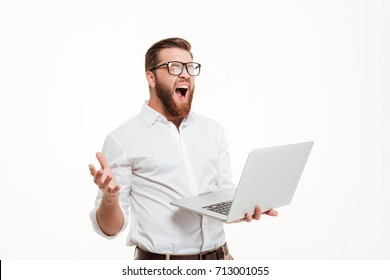 Angry upset bearded man in eyeglasses holding laptop and screaming isolated over white background