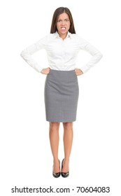 Angry upset young business woman standing isolated in full length. Funny image of mixed race Asian Caucasian female model.
