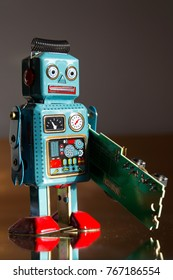 Angry vintage tin toy robot carries green computer circuit board, artificial intelligence concept