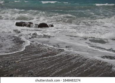 Angry waves smash into rocks on the beach