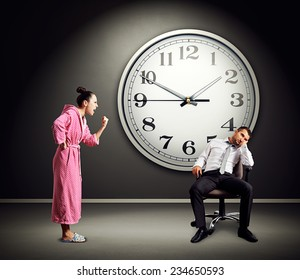 angry wife screaming at lazy husband. photo in dark room with big clock on the wall