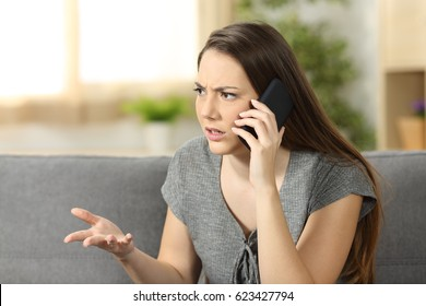 Angry woman arguing during a phone call sitting on a couch in the living room at home