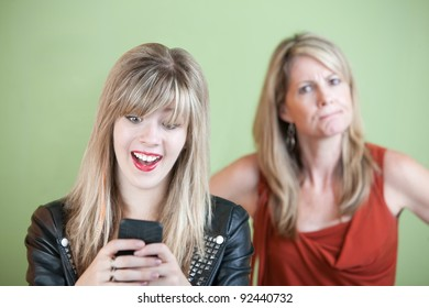 Angry woman behind excited teen on mobile phone