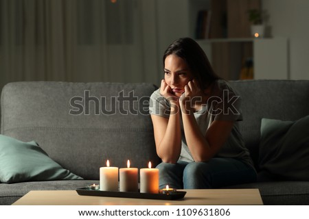 Angry woman boring during a blackout in the night sitting on a couch in the living room at home