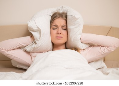 Angry woman disturbed with a noise trying to sleep and covering her ears with a pillow.