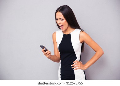 Angry woman in dress shouting on smartphone over gray background
