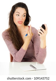 An angry woman is giving her mobile phone the finger. Isolated on white.