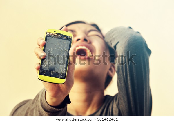 Angry woman holding broken smart phone